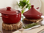 Red cookware on potholders made from corks