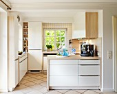 Pale fitted kitchen with wooden worksurfaces, lattice windows and tiled floor