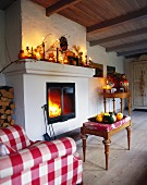 A country house-style living room with autumnal decorations and an upholstered stool and armchair with matching checked covers in front of an open fire