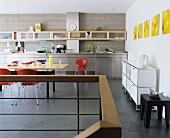 A spacious, modern kitchen with stainless steel work tops and maple wood wall shelves and dining table