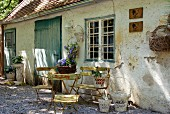 Retro garden furniture in front of a house with a flaking facade