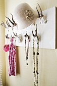 Coat rack with antler hooks; hat, necklaces and jewellery hanging on hooks