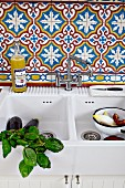 Basil sprigs and vegetables in a white ceramic sink with Moroccan tiles on the wall behind