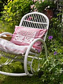 A rocking chair in a summery garden with a decorative, embroidered cushion