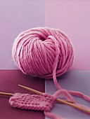 A pink ball of wool with knitting needles on a pink and purple surface