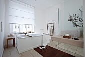 A spacious bathroom in white with touches of brown