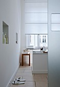 A white bathroom with a window, a free-standing bathtub, a tiled floors and a wall niche used as storage