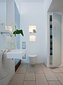 A white bathroom with a wash basin, a suspended toilet and a built in wall cupboard