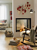 Homemade heart-shaped felt bags hanging from a twig above and open fire place
