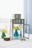 Easter decorations with a zinc garden lantern, narcisi in a vase and quail's eggs