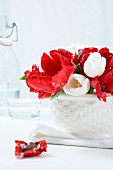 Red and white tulips in a porcelain bowl