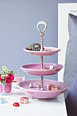 Jewellery and chocolates on pink cake stand