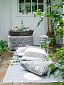 Outdoor rug and floor cushions in front of wicker tray on pouffe