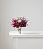Bouquet of sweet william, sweet peas and shepherd's purse in vase on white table