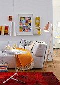 A living room with a sofa, a floor lamp, a side table and a pendant lamp