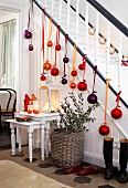 A banister and hallway decorated with Christmas baubles and candles