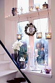 A window sill next to a stairway decorated for Christmas