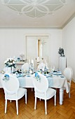 A table laid for Christmas dinner decorated in sliver, blue and white