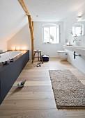 Modern, attic bathroom with fitted bathtub