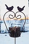 Aus Zweigen gebasteltes Windlicht auf Eisengestell mit Vogelmotiv