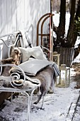 A reindeer fur and cushions on an iron bench in a snowy garden
