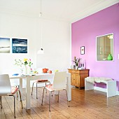 A living room with floor boards, a white dining table, a bench and a wooden chest of drawers against a violet wall