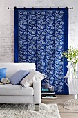 Blue and white printed wall hanging behind white sofa in living room