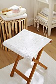 A folding stool with a white knitted seat