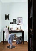Photos and miniature Eiffel Tower on desk with swivel chair and decorative letters on wall