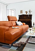 Brown leather sofa and piano in living room