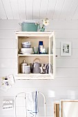 Crockery in small, wall-mounted cabinet in Scandinavian summer house