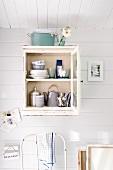 Crockery in small, wall-mounted cabinet in Scandinavian summer house