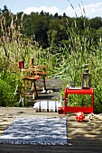 Directors' chairs & small table on boardwalk amongst reeds