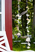 Wind chimes made from seashells & feathers hanging outside summer house