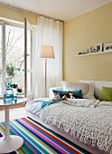 Interior with open sofabed as guest bed & multicoloured striped rug