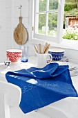 A blue knitted cloth on a kitchen table in front of a window