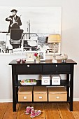 Storage boxes under a black console table against a wall hung with a framed photograph