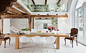 An open-plan dining room in white with a wooden beam ceiling and a glazed gallery
