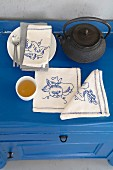 A teapot, a tea bowl and linen napkins embroidered with various motifs on a blue chest of drawers
