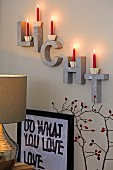 Red candles on decorative letters on a wall