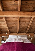 Bedroom with bed below sloping wooden ceiling