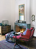 An antique chaise lounge with a red velvet cover and a side table next to an open fire