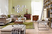 Pale chaise sofa, antique chest of drawers and bookcase with ladder in living room with pale green wall
