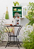 Crockery in small, wall-mounted cabinet above espresso machine on table on balcony