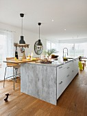 A modern kitchen island with a seating place and bar stools