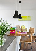 A seating area with bar stool and a pendant lamp at a modern kitchen island