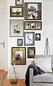Wohnraum mit Sofa & dekorativer Bildergalerie an Zimmerwand