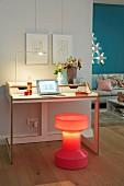 A desk with an illuminated stool