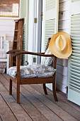 Wooden armchair with seat cushion on veranda