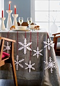 A table laid for Christmas decorated with paper snowflakes